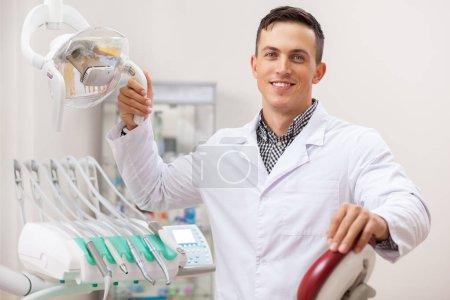 Photo pour Joyeux beau dentiste masculin souriant joyeusement, travaillant à son bureau, copier l'espace. Un dentiste professionnel attend des patients à sa clinique. Examen dentaire, dentisterie et médecine concept de l'industrie - image libre de droit