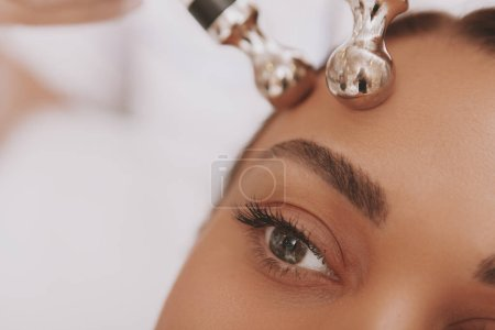 Photo for Cropped close up of a female patient receiving microcurrent facial skin treatment at beautician office. Selective focus on beautiful woman eye, receiving face care therapy. Hardware cosmetology - Royalty Free Image