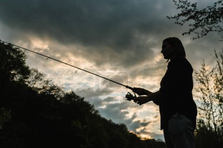 Silhouette of a fisherman. Young woman fishing on ...