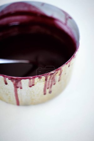 Red wine reduction, on a white background.