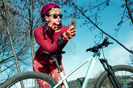 Photo for Young woman with bike helmet and sunglasses makes selfie in a natural park - Royalty Free Image