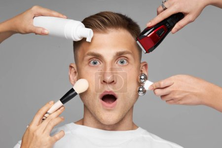 Photo pour Cosmétologie masculine. Soins du visage pour un modèle africain. Rouleau de jade, rasoir électrique, pinceaux de maquillage et liquides dans une bouteille près d'un visage surpris d'un homme. Photo de haute qualité - image libre de droit
