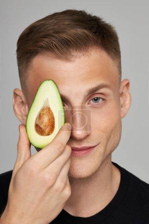 Photo pour Avocat pour le visage. Soins de la peau avec des vitamines naturelles. Modèle masculin contient des fruits frais près du visage. Photo de haute qualité - image libre de droit