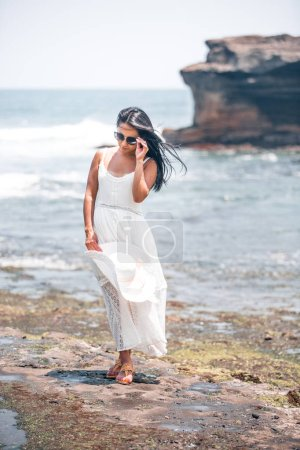 Photo for Woman in a white long dress on the seashore touching her glasses - Royalty Free Image