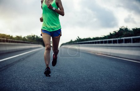cropped image of young fitness woman running on city road