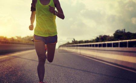 Photo pour Image recadrée de jeune femme de forme physique courant sur la route de la ville - image libre de droit