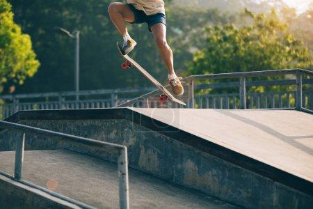 Cropped image of skateboarder skateboarding on skatepark ramp
