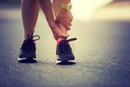 sportswoman suffering from sports injury while running on city street