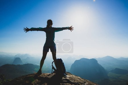 Photo for Successful cheering young woman hiker with outstretched arms on mountain peak during sunrise - Royalty Free Image