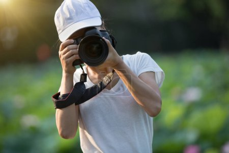 Female photographer taking pictures with professional photo camera outdoors