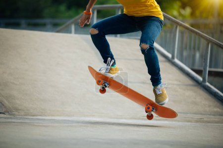Cropped image of skateboarder skateboarding at skatepark