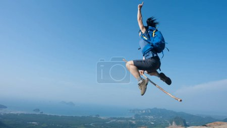 Woman jumping on mountain top cliff edge