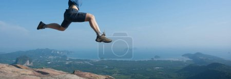 Young woman jumping on mountain peak cliff edge