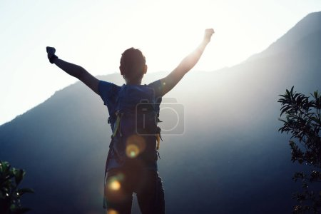 successful female hiker with outstreched arms standing on mountain top during sunrise