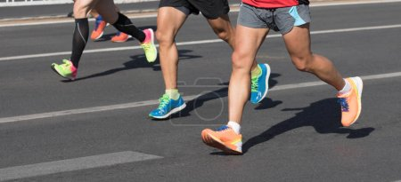 Cropped image of marathon runners running on city road