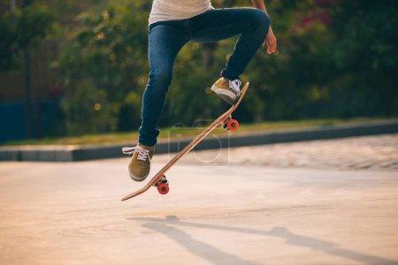 Cropped image of skateboarder sakteboarding on parking lot
