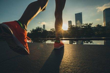 Healthy lifestyle woman runner legs running on sunrise city