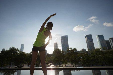 Fitness woman runner warming up before running