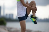 Healthy lifestyle woman runner stretching legs before running