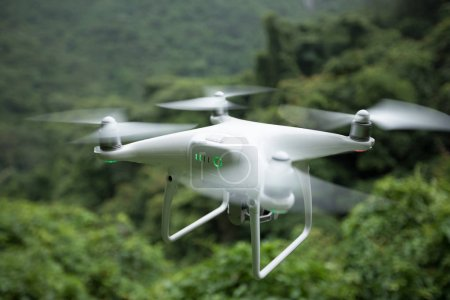 Photo for White drone with camera flying over tropical forest - Royalty Free Image
