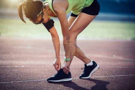 Photo for Sportswoman tying shoelace before run on stadium - Royalty Free Image