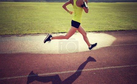 Young sportswoman running on stadium tracks