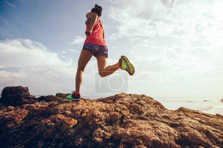 Photo pour Jeune femme fitness trail runner courant vers le sommet rocheux sur le bord de la mer - image libre de droit