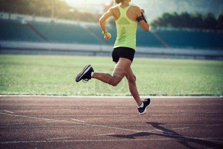 Photo for Sportswoman running on stadium tracks - Royalty Free Image