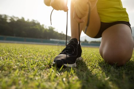 Photo for Young fitness woman runner tying shoelace on stadium tracks - Royalty Free Image