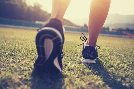 Photo for Fitness sportswoman legs running on stadium grass - Royalty Free Image