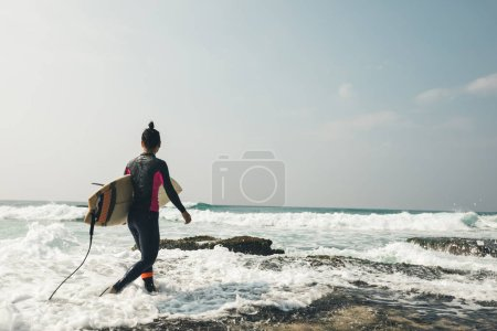 Photo for Young woman surfer with surfboard going to surf - Royalty Free Image