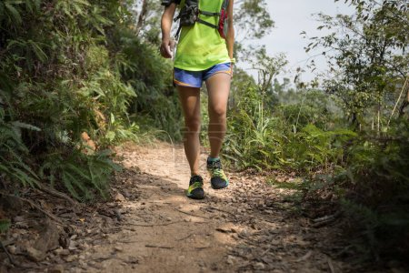 Photo for Young fitness woman trail runner running on rocky trail - Royalty Free Image