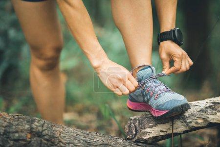 Photo pour Sportswoman trail runner attacher lacet de chaussure en forêt - image libre de droit