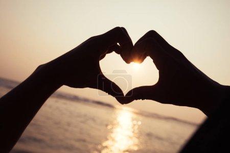 Photo pour Coucher de soleil qui brille par coeur en forme de mains - image libre de droit