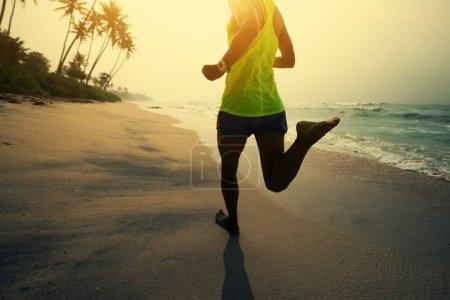 Foto de Concepto de fitness estilo de vida saludable, joven, correr en playa tropical durante salida del sol en la mañana - Imagen libre de derechos