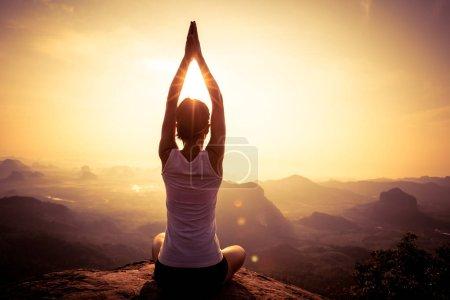 Photo for Young fitness yoga woman meditating on sunrise mountain peak - Royalty Free Image