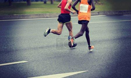 Photo for Marathon runner legs running on city road - Royalty Free Image
