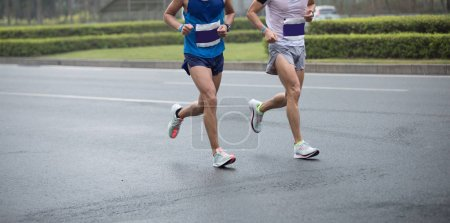 Photo for Marathon runner legs running on city road - Royalty Free Image