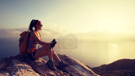Photo for Young woman hiker sitting at sunrise seaside mountain peak - Royalty Free Image