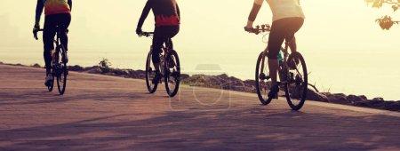 Photo pour Cyclistes à vélo de montagne sur le bord de mer - image libre de droit