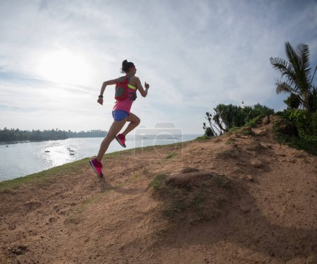 Photo for Woman trail runner running on seaside hill - Royalty Free Image