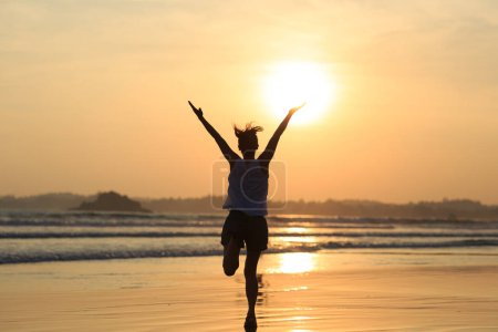 Photo for Happy Free Woman running on the beach at Sunset - Royalty Free Image
