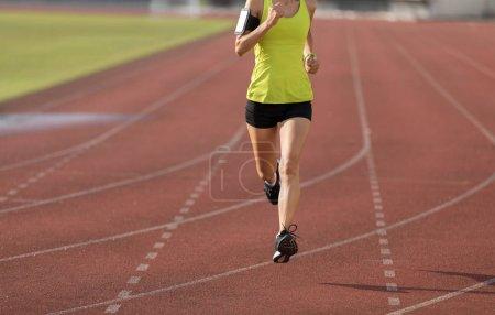 Photo for Fitness sportswoman running on stadium race tracks - Royalty Free Image