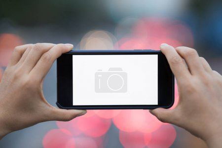 Photo for Cropped view of person taking photo on cellphone in city - Royalty Free Image