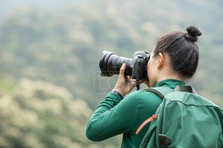 Photo for Woman photographer taking photo on spring forest mountain - Royalty Free Image