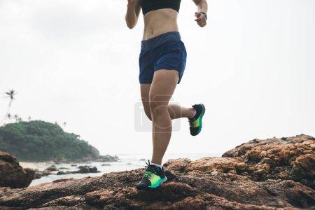 Photo pour Femme courant vers le sommet rocheux au bord de la mer - image libre de droit