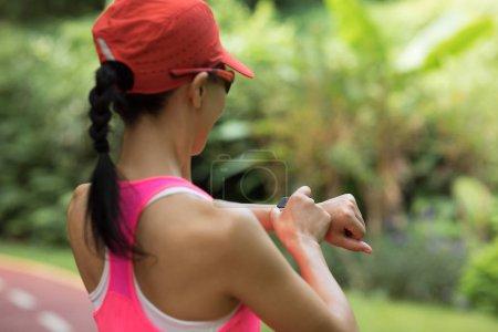 Photo pour Femme réglant sa balade avant de courir sur le sentier du parc - image libre de droit