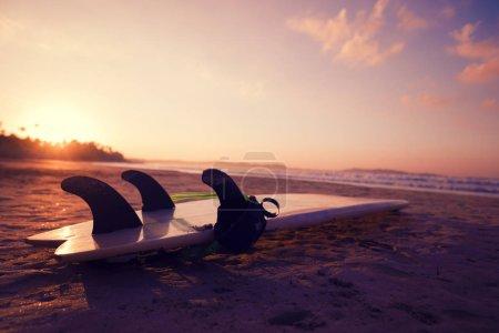 Photo pour Surfboard sur une plage de sable au lever du soleil - image libre de droit