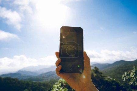 Photo pour Main utilisant le téléphone portable prenant des photos dans la nature lever de soleil - image libre de droit