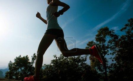 Photo pour Fitness femme coureur courir sur le lever du soleil montagne bord - image libre de droit